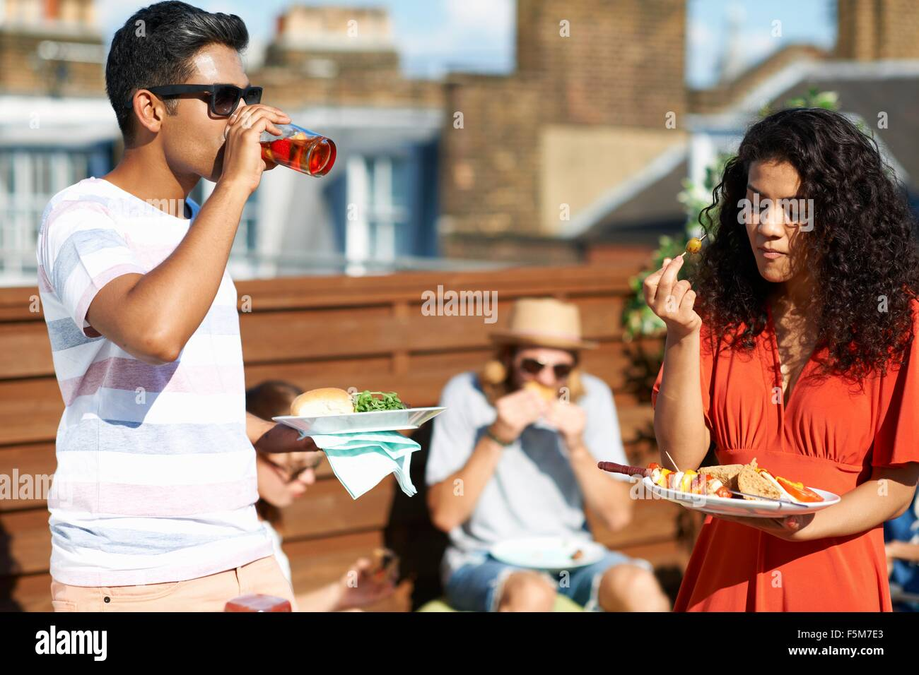 Friends eating party food and drinking at rooftop party - Stock Image