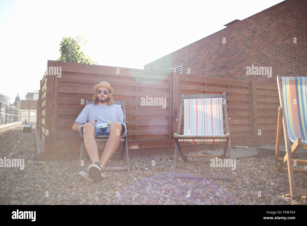 Young man alone on deckchair at rooftop party - Stock Image