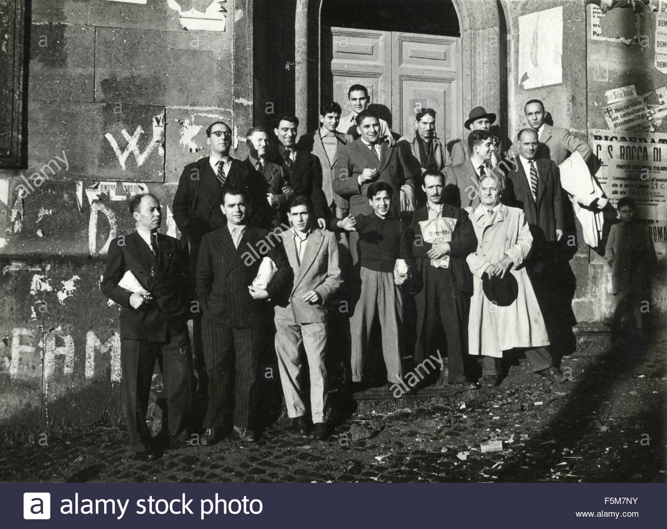 A large group next to walls and defaced posters, Italy - Stock Image