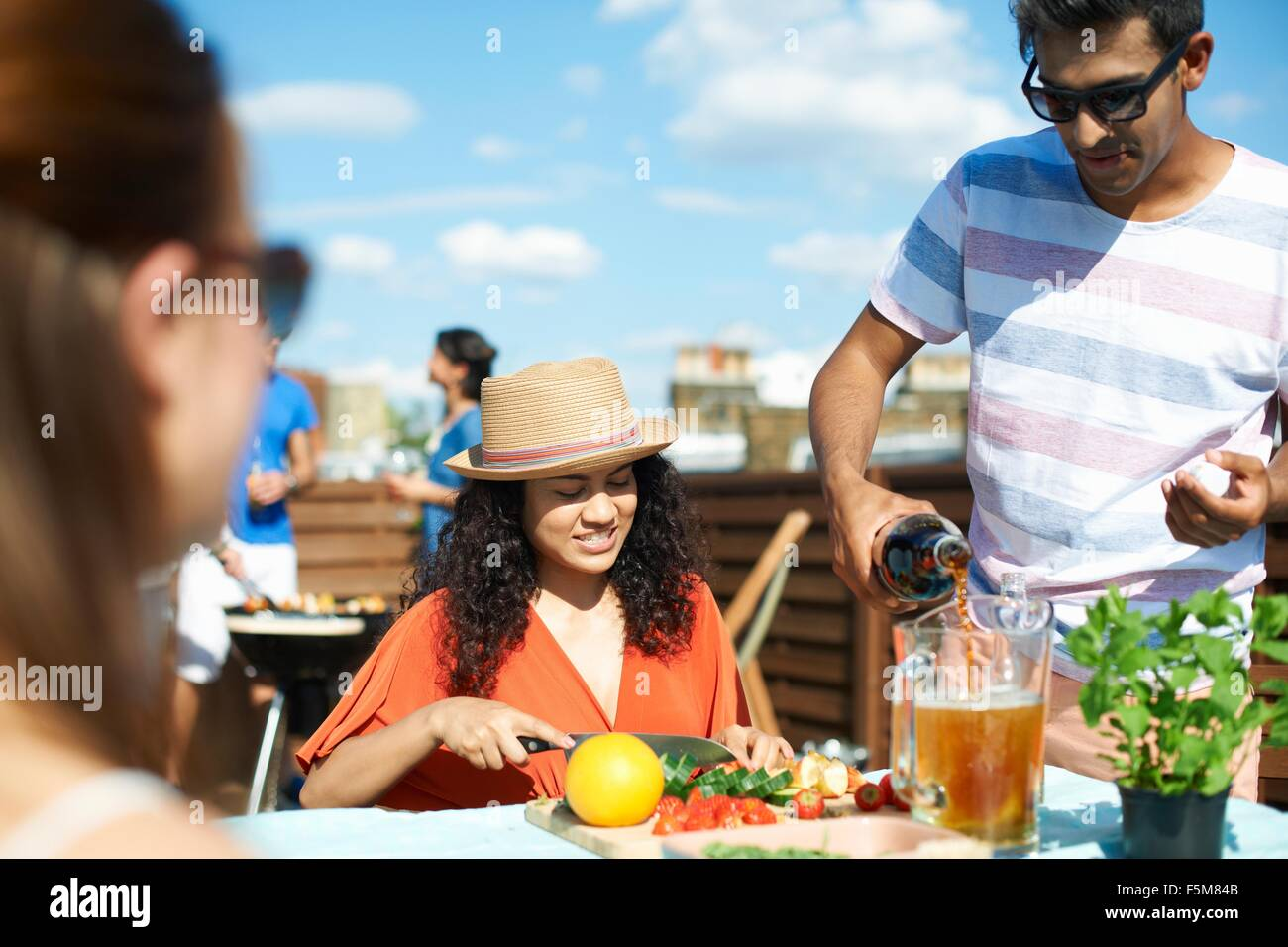 Adult friends preparing fresh punch cocktail at rooftop party - Stock Image