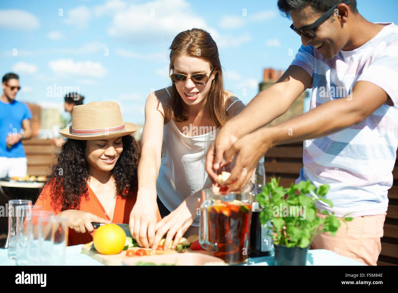Adult friends preparing fruit for punch cocktail at rooftop party - Stock Image