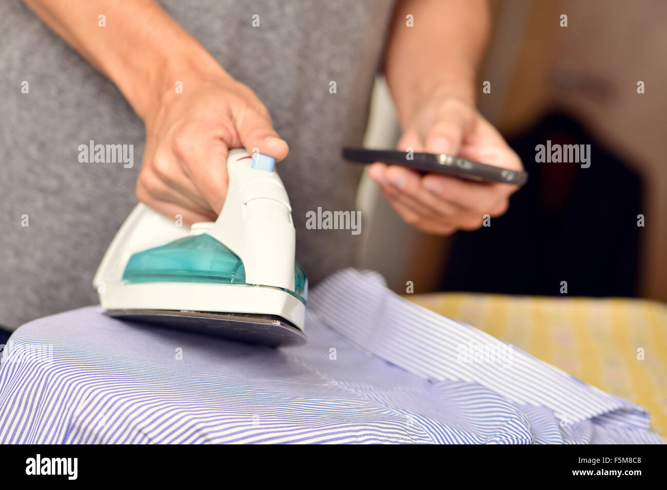 closeup of a young man ironing clothes and using a smartphone at the same time - Stock Image