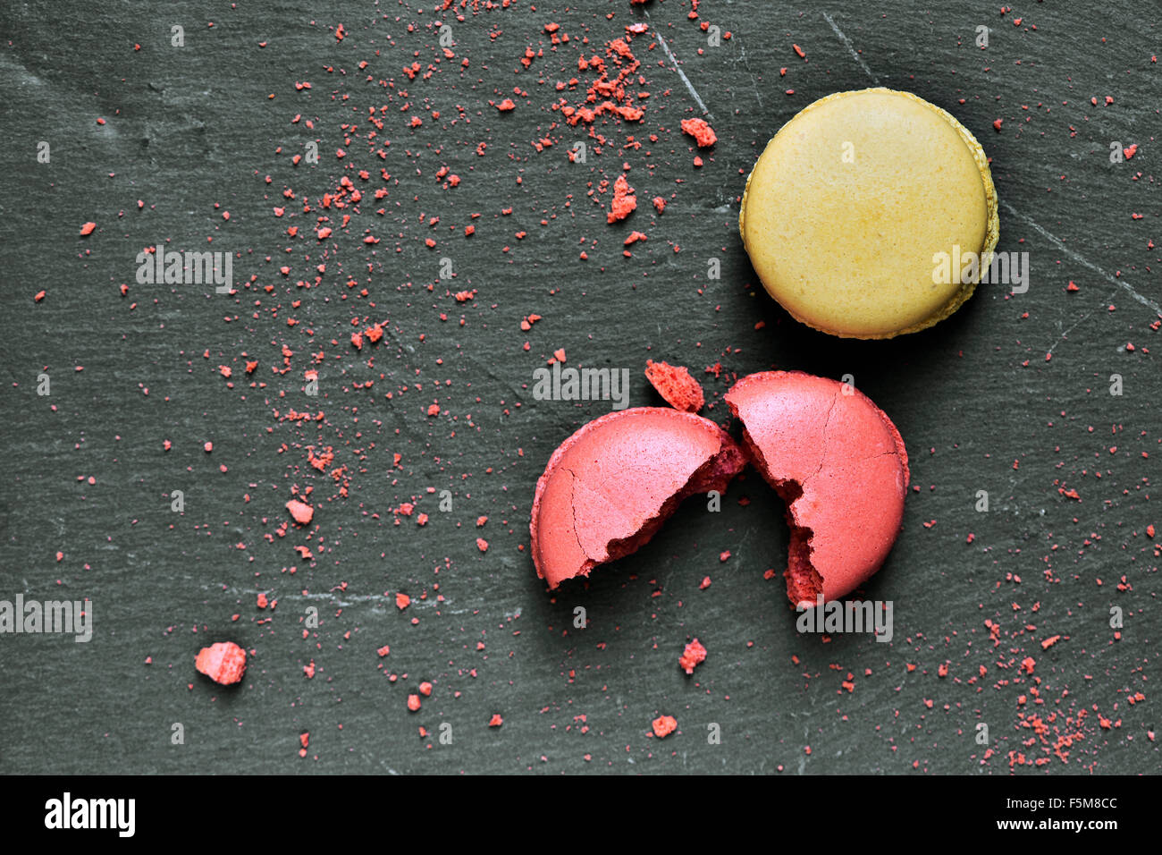 some appetizing macarons of different flavors on a slate surface - Stock Image