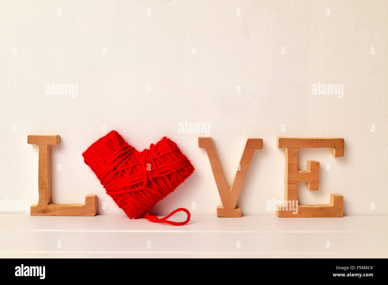 some wooden letters and a heart-shaped coil of red yarn forming the word love - Stock Image
