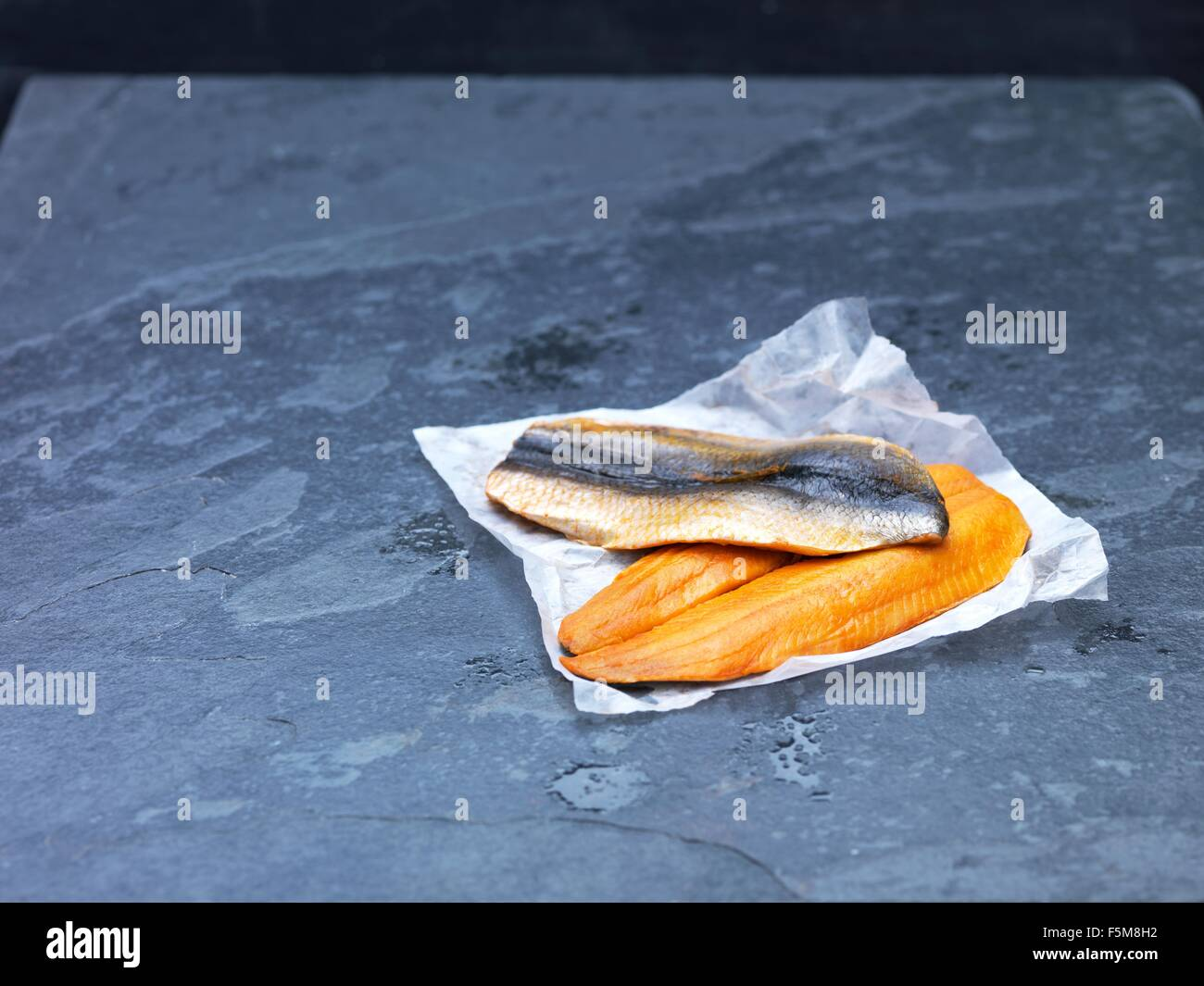 High angle view of raw Scottish kipper fillets on baking paper and slate - Stock Image