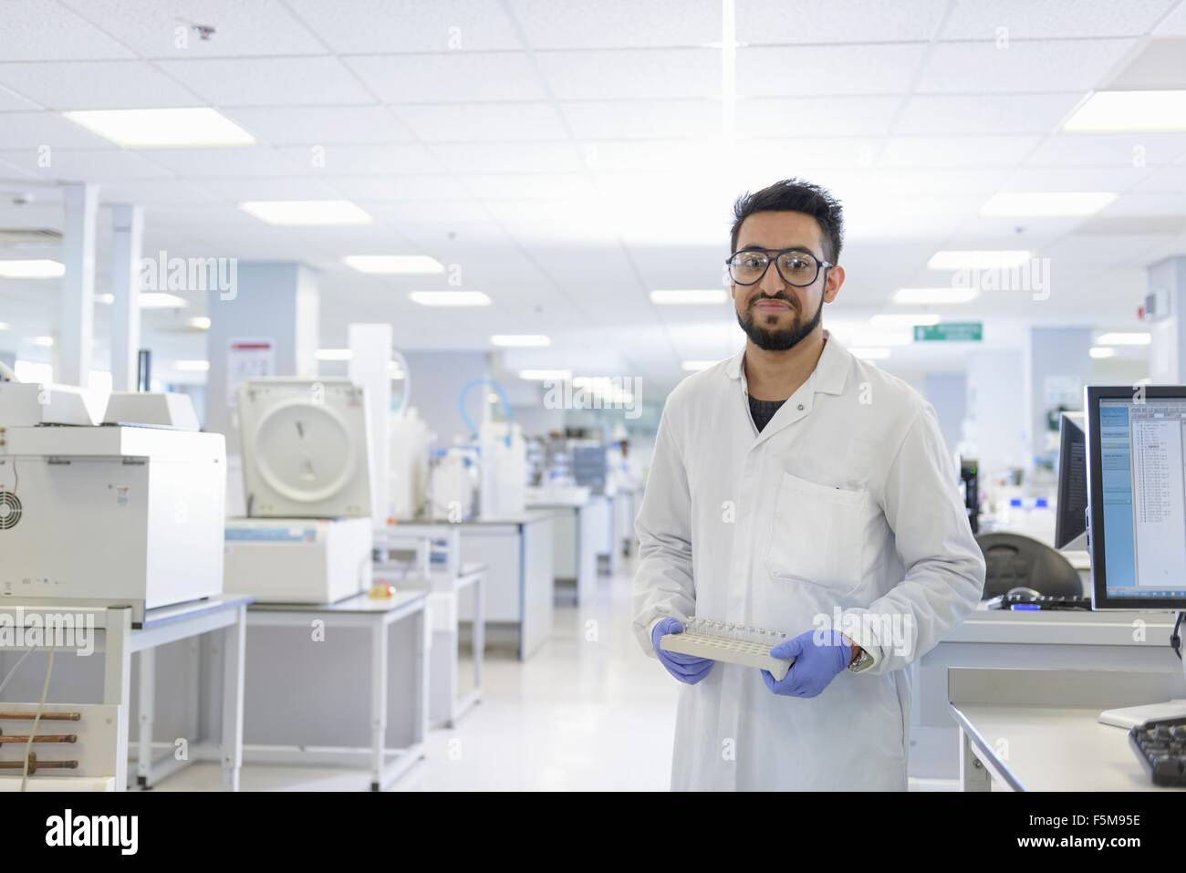 Portrait of scientist with analyst samples in testing laboratory - Stock Image