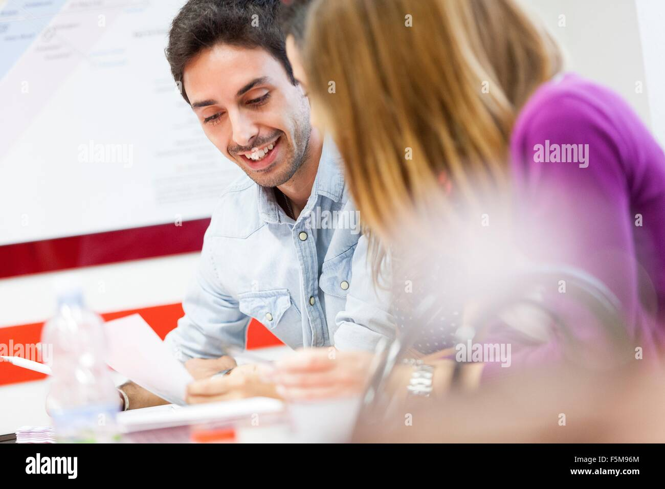 Man and woman sitting together, laughing - Stock Image