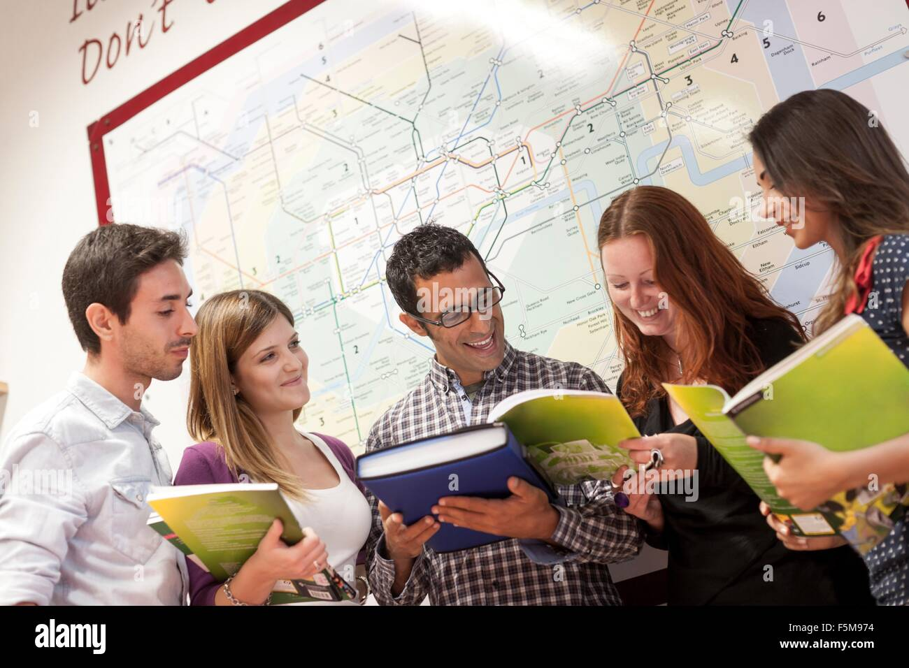 Small group of people, looking through study books - Stock Image