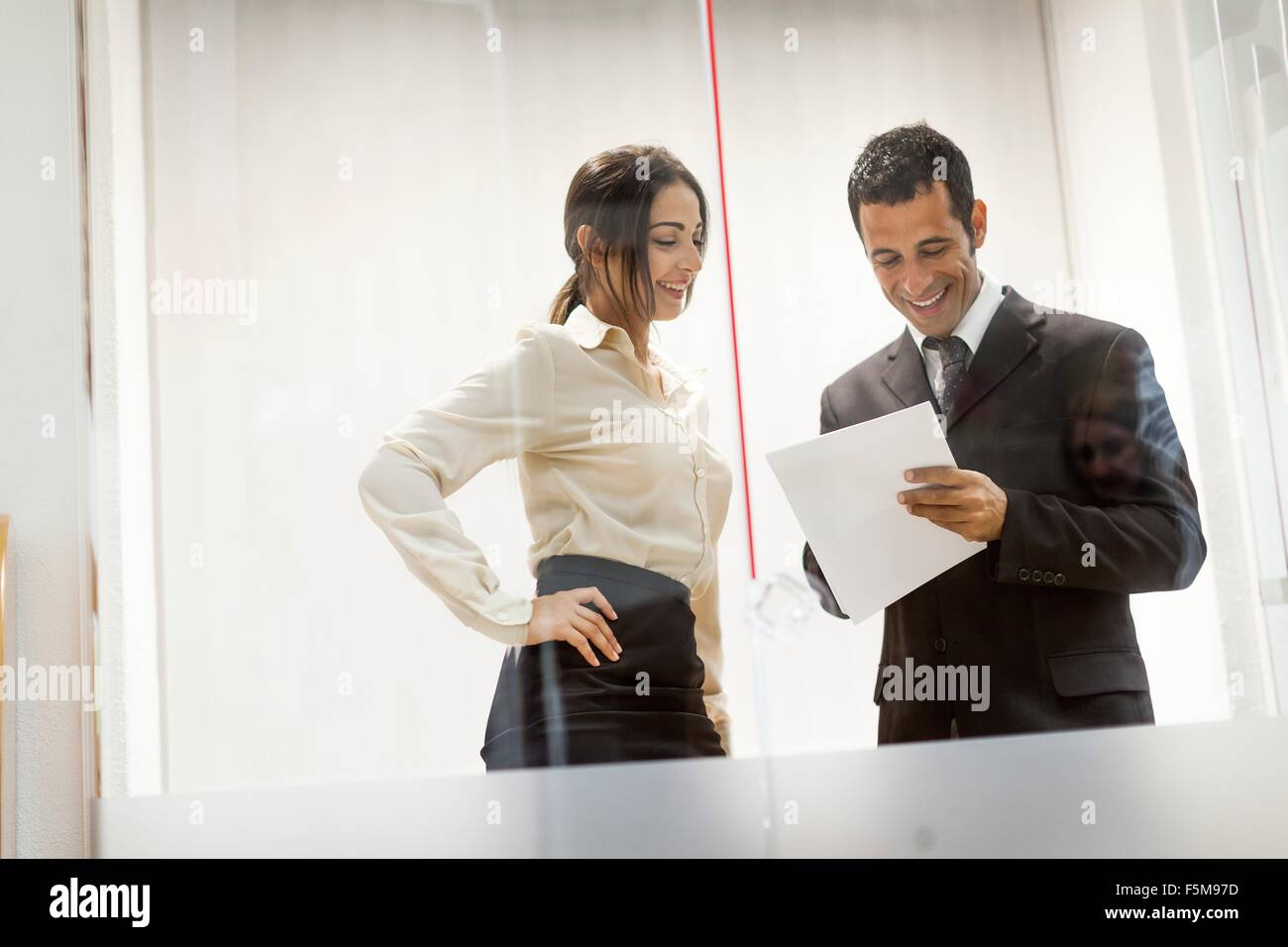 Businessman and businesswoman looking at documents, having conversation - Stock Image