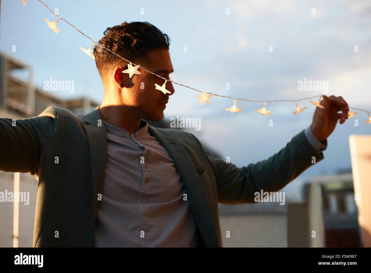 Man handing garden lights for early evening party - Stock Image