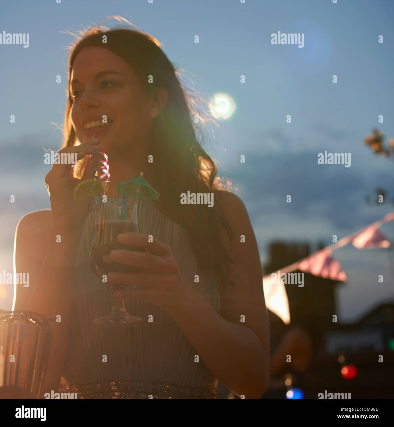 Woman at early evening party - Stock Image