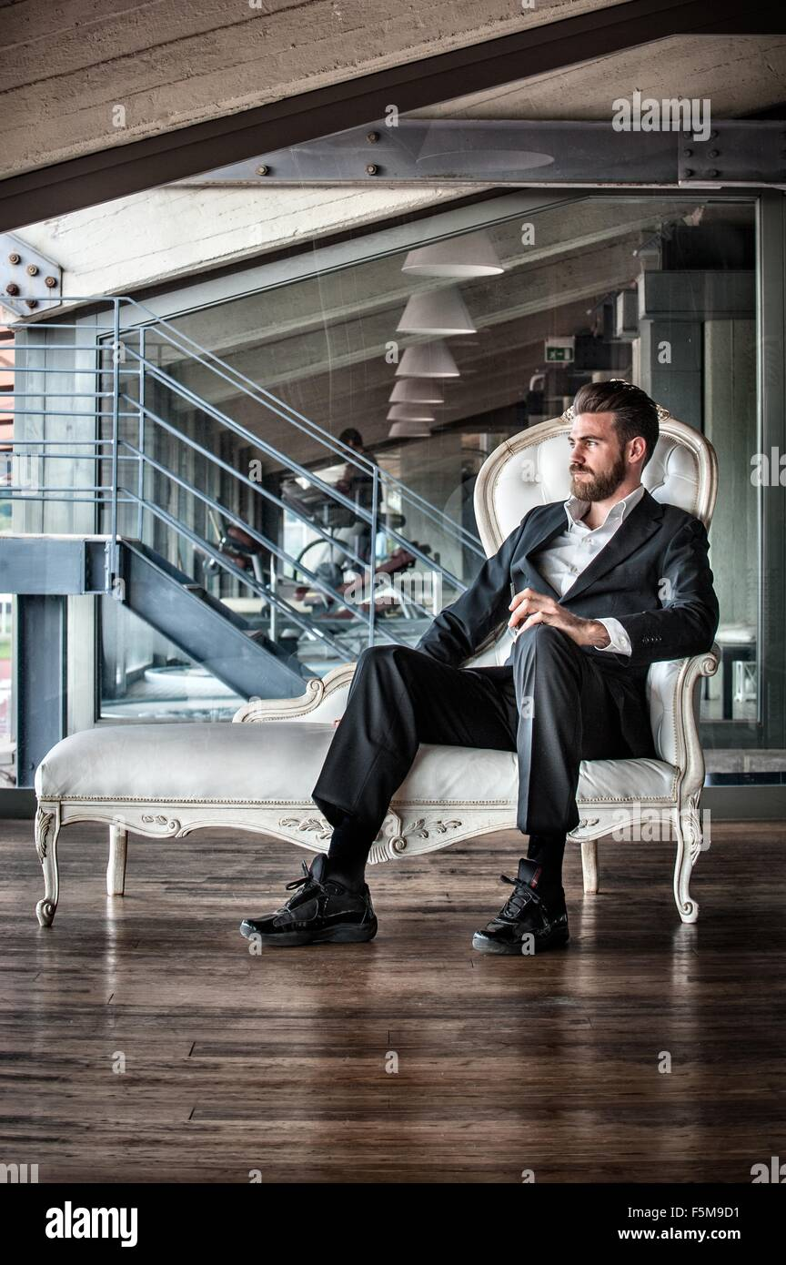 Mid adult man wearing suit sitting on chaise lounge looking away - Stock Image