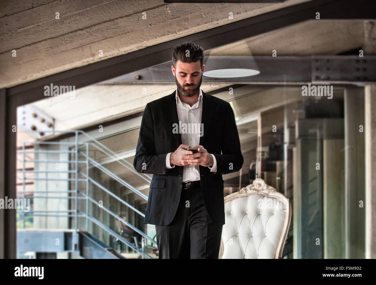 Mid adult man wearing suit holding smartphone looking down - Stock Image