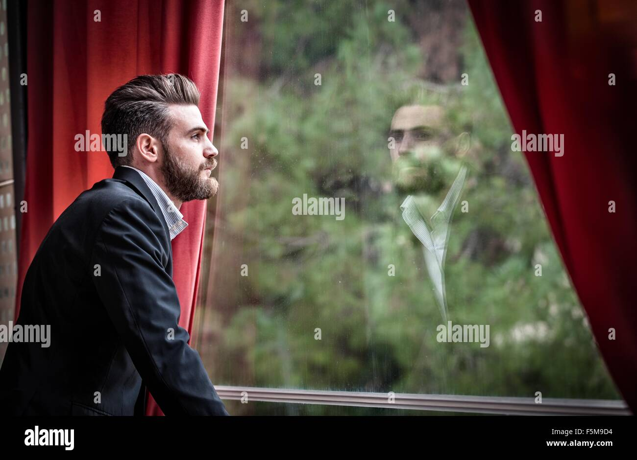 Side view of mid adult man wearing suit looking out of window - Stock Image