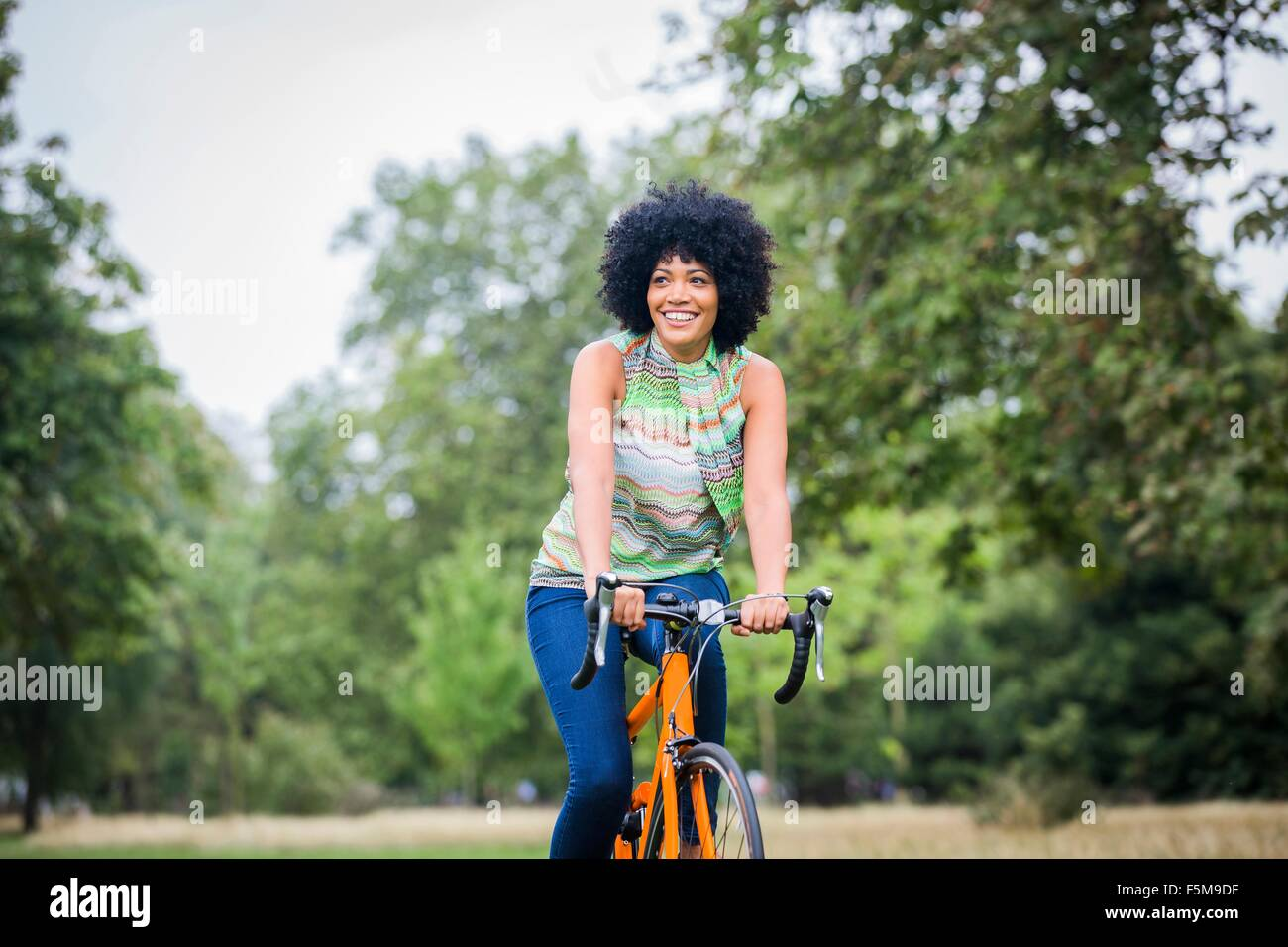 Front view of mature woman with afro riding bicycle looking away smiling - Stock Image