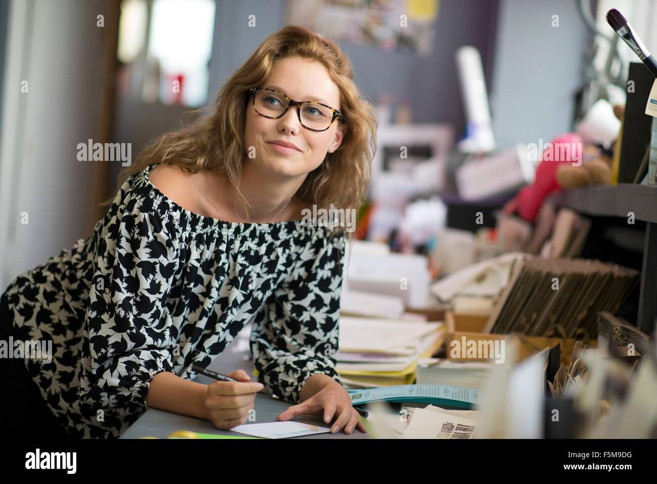 Female print designer drawing designs in workshop - Stock Image