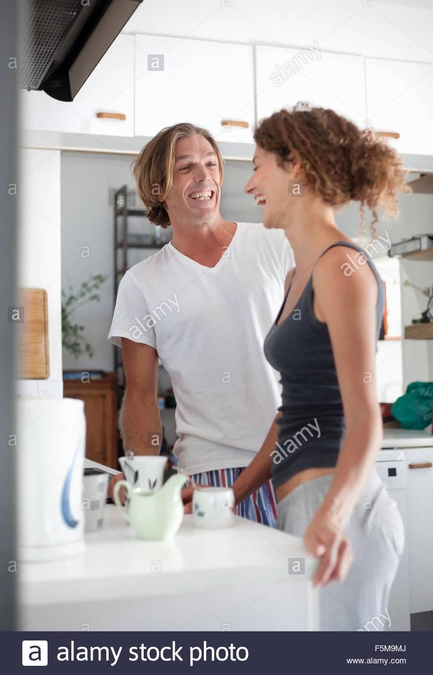 Couple in sleepwear, making coffee in morning - Stock Image