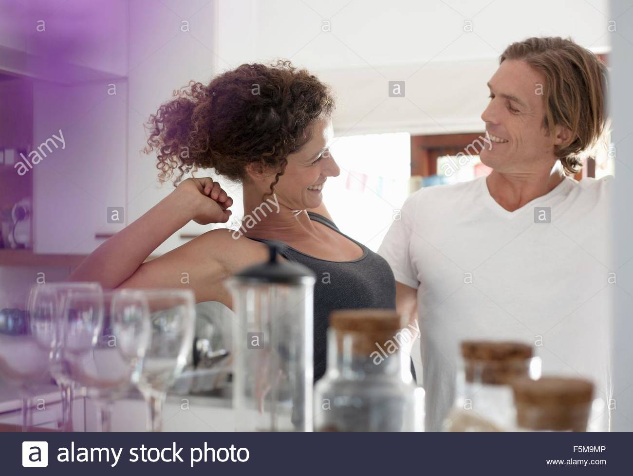 Couple in sleepwear, in kitchen, stretching, smiling - Stock Image