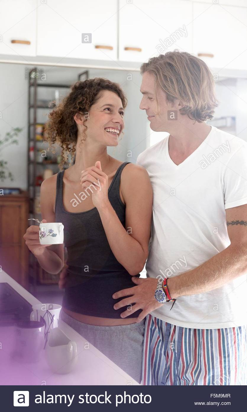 Couple in sleepwear, in kitchen, smiling - Stock Image