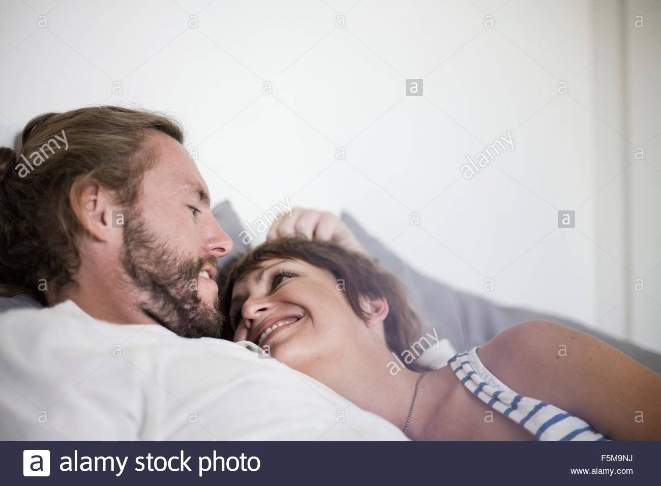 Couple in loving embrace in bed - Stock Image