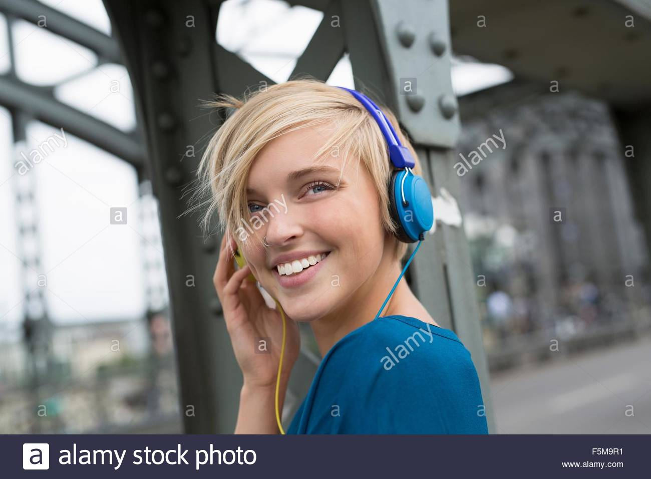 Happy young woman wearing headphones on bridge looking over her shoulder - Stock Image