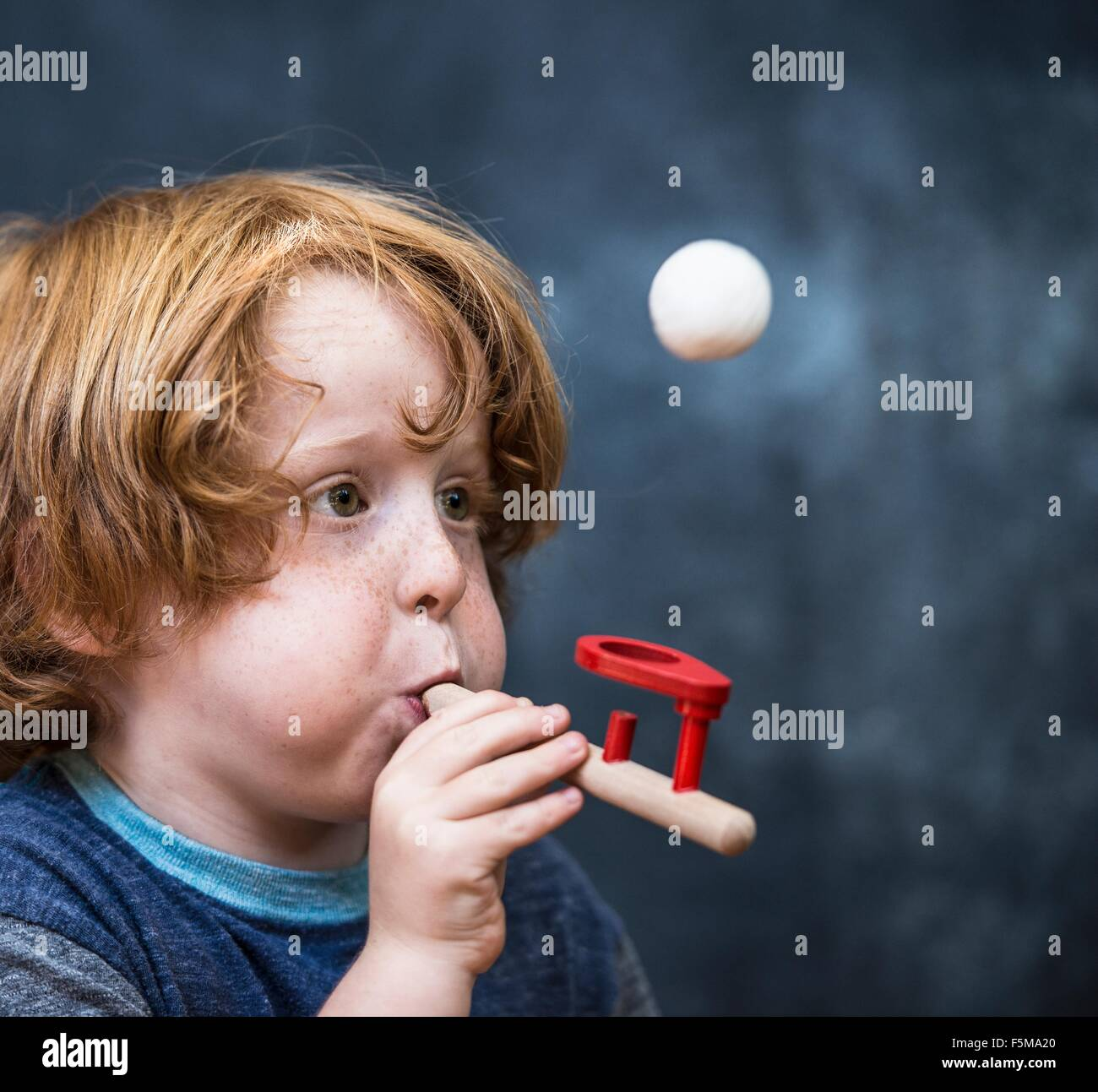 Young boy playing game, blowing ping pong ball in air - Stock Image