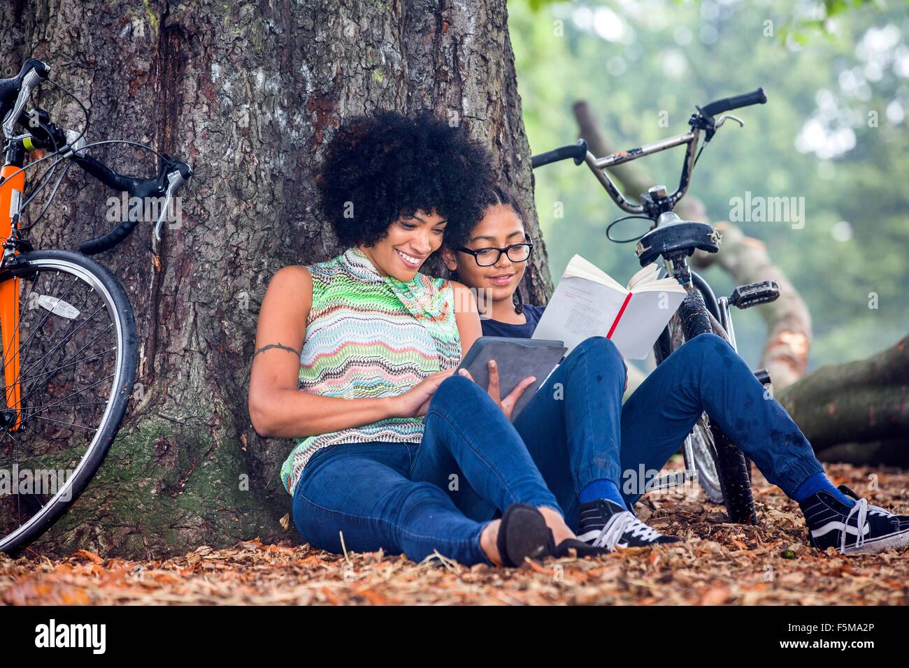 Mature woman and son sitting against park tree reading book and digital tablet - Stock Image