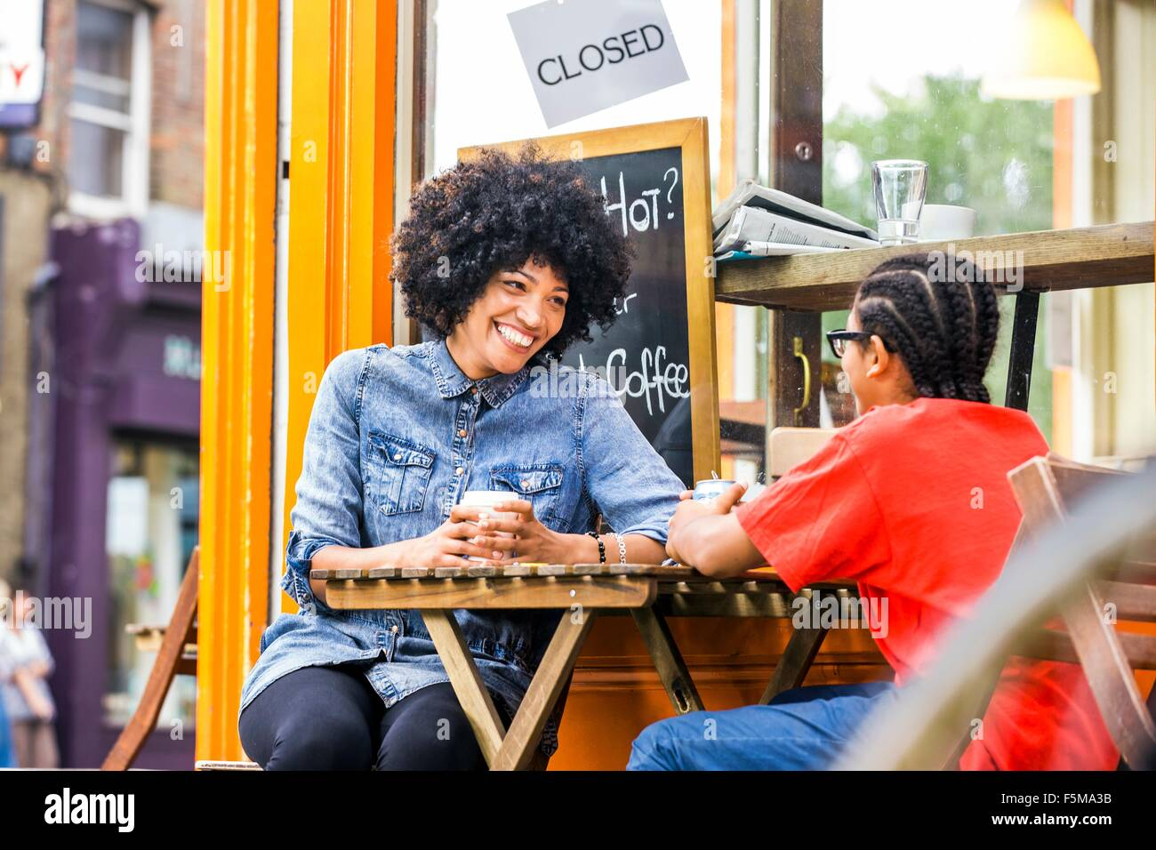 Boy and mother chatting at sidewalk cafe - Stock Image
