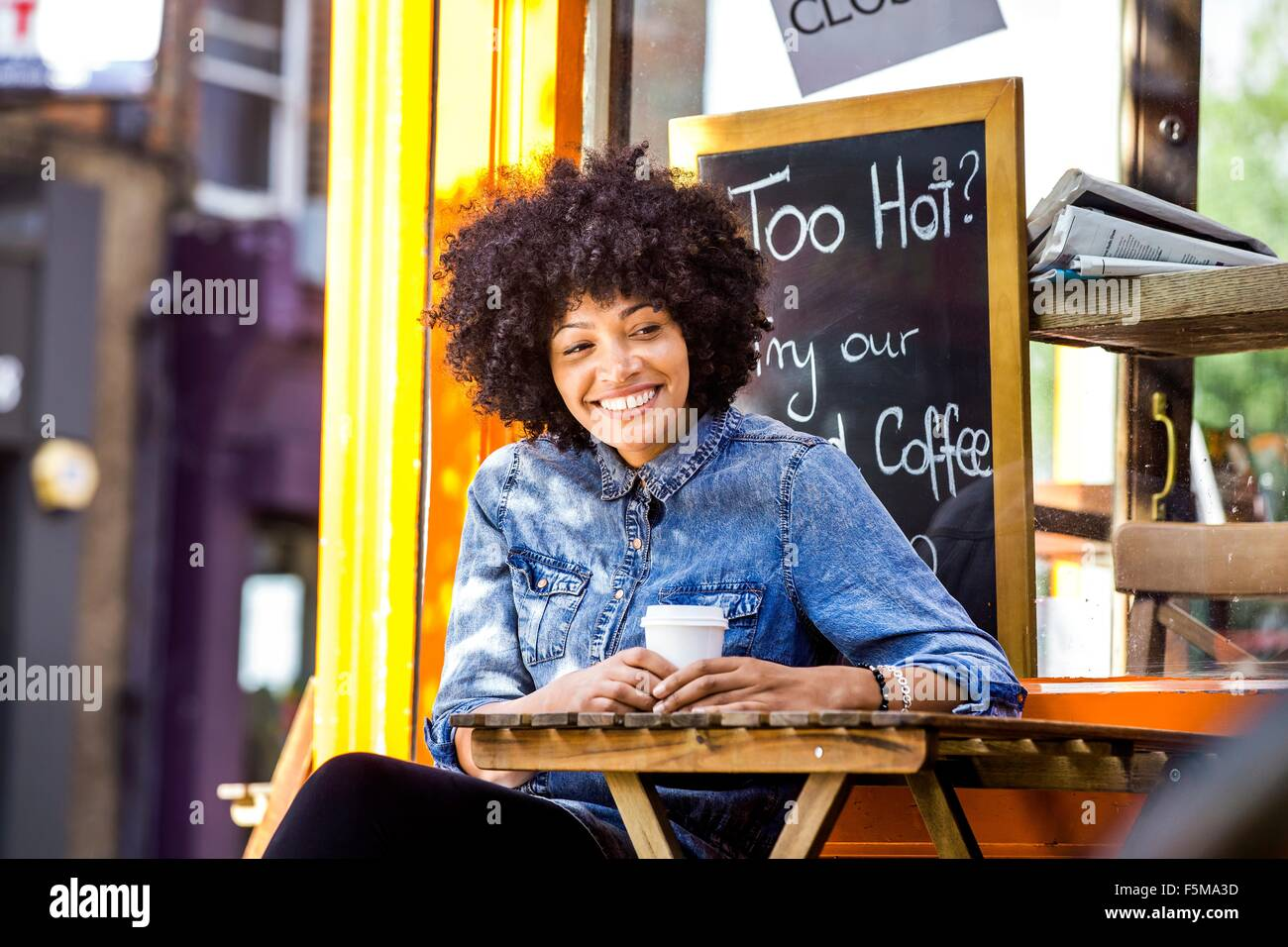 Happy mature woman drinking takeaway coffee and sidewalk cafe - Stock Image