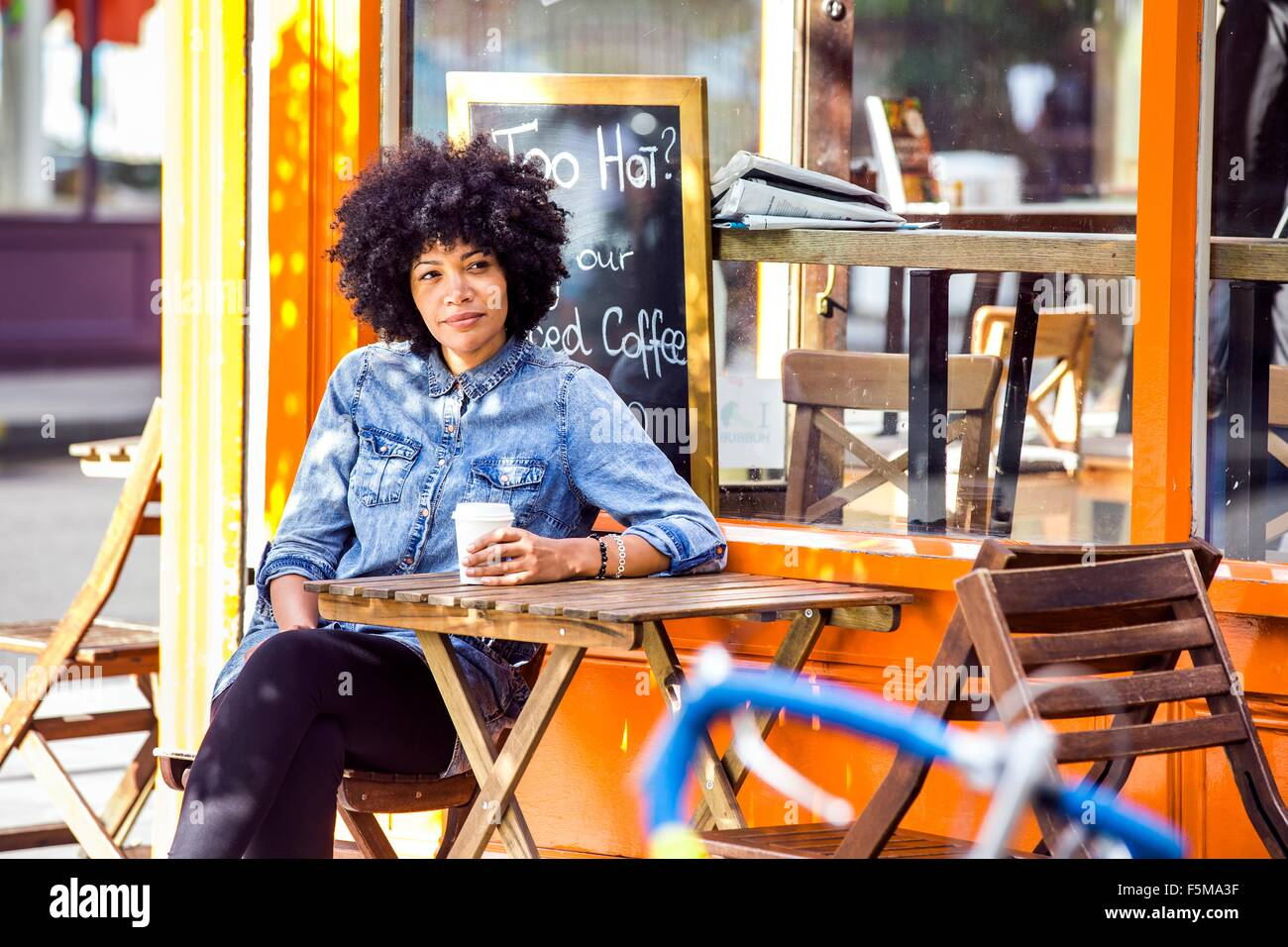 Mature woman drinking takeaway coffee and sidewalk cafe - Stock Image