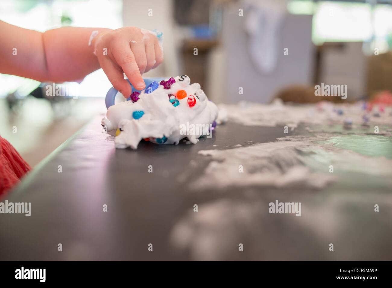 Young girl playing messy play at table - Stock Image