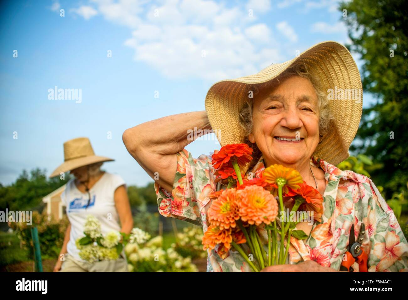Senior woman holding onto straw hat and flowers on farm - Stock Image