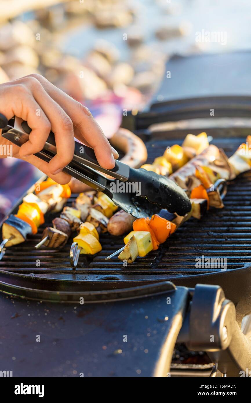 Young mans hand using tongs to turn sausages and kebabs on barbecue griddle - Stock Image