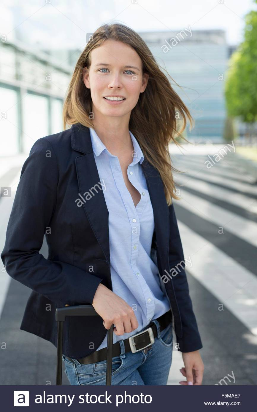 Portrait of young businesswoman with wheeled suitcase at airport - Stock Image