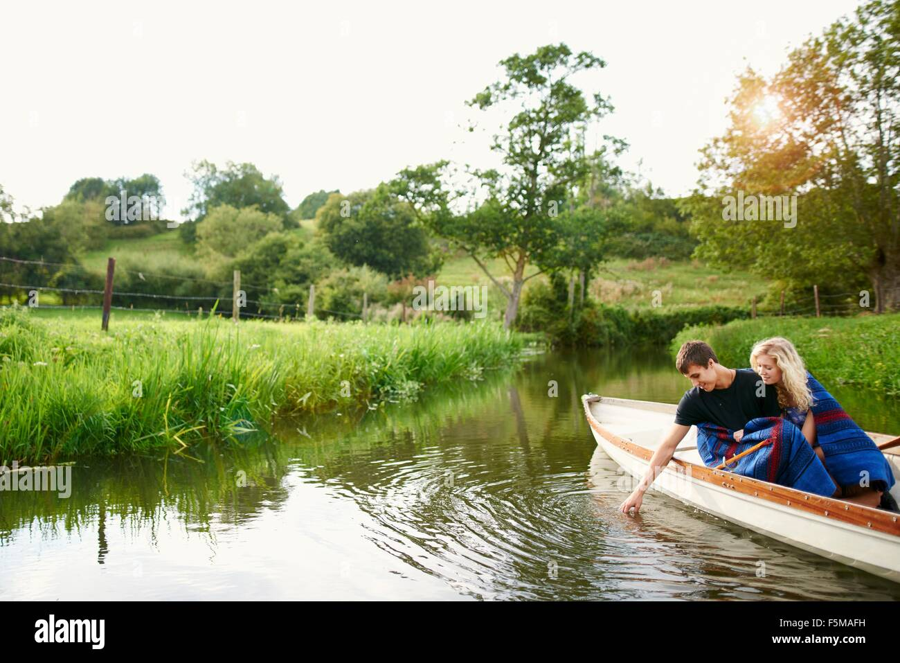 Young man with girlfriend touching water from river  rowing boat - Stock Image