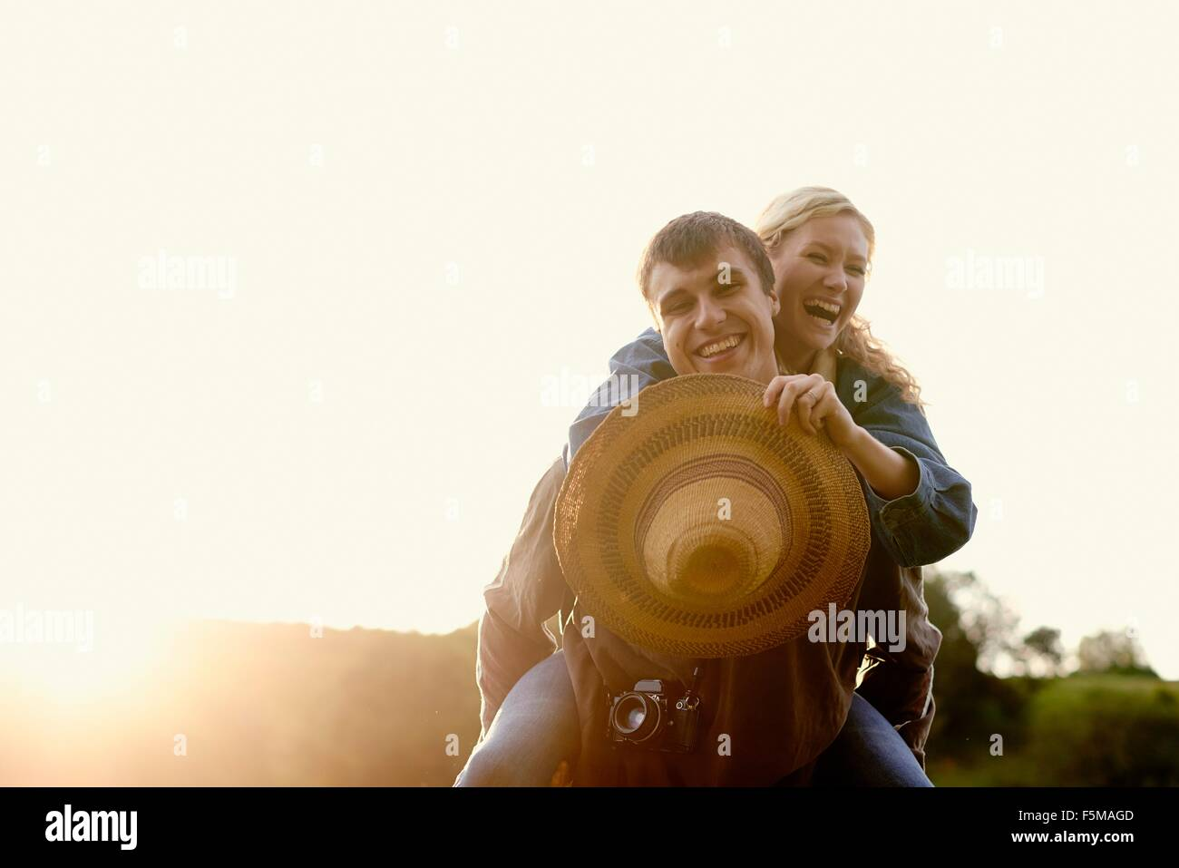 Portrait of young man giving girlfriend a piggyback - Stock Image