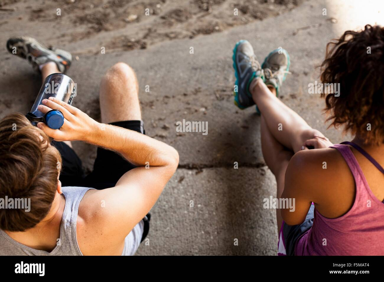 Overhead view of joggers taking break on kerb - Stock Image