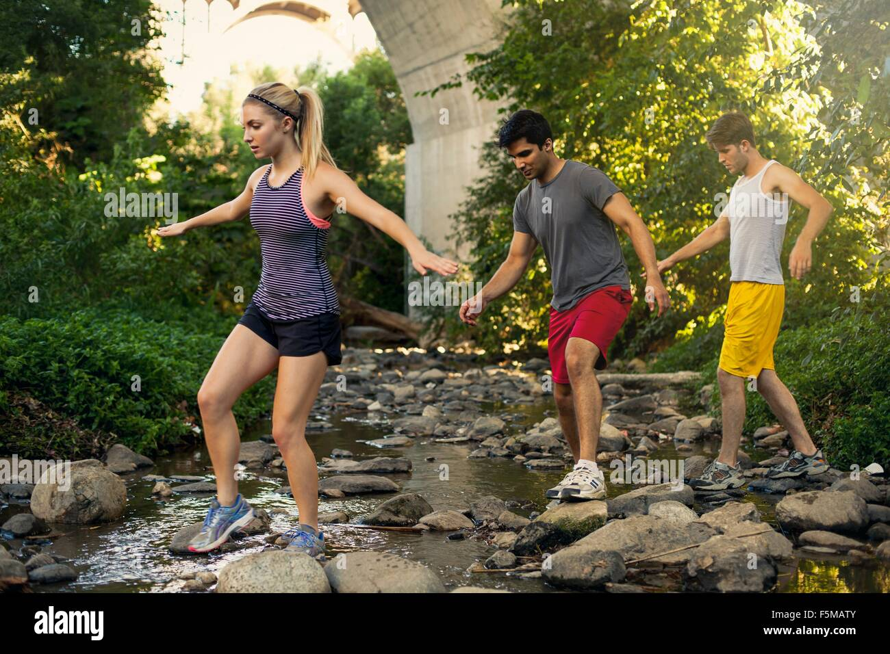 Joggers crossing stream under arch bridge, Arroyo Seco Park, Pasadena, California, USA - Stock Image
