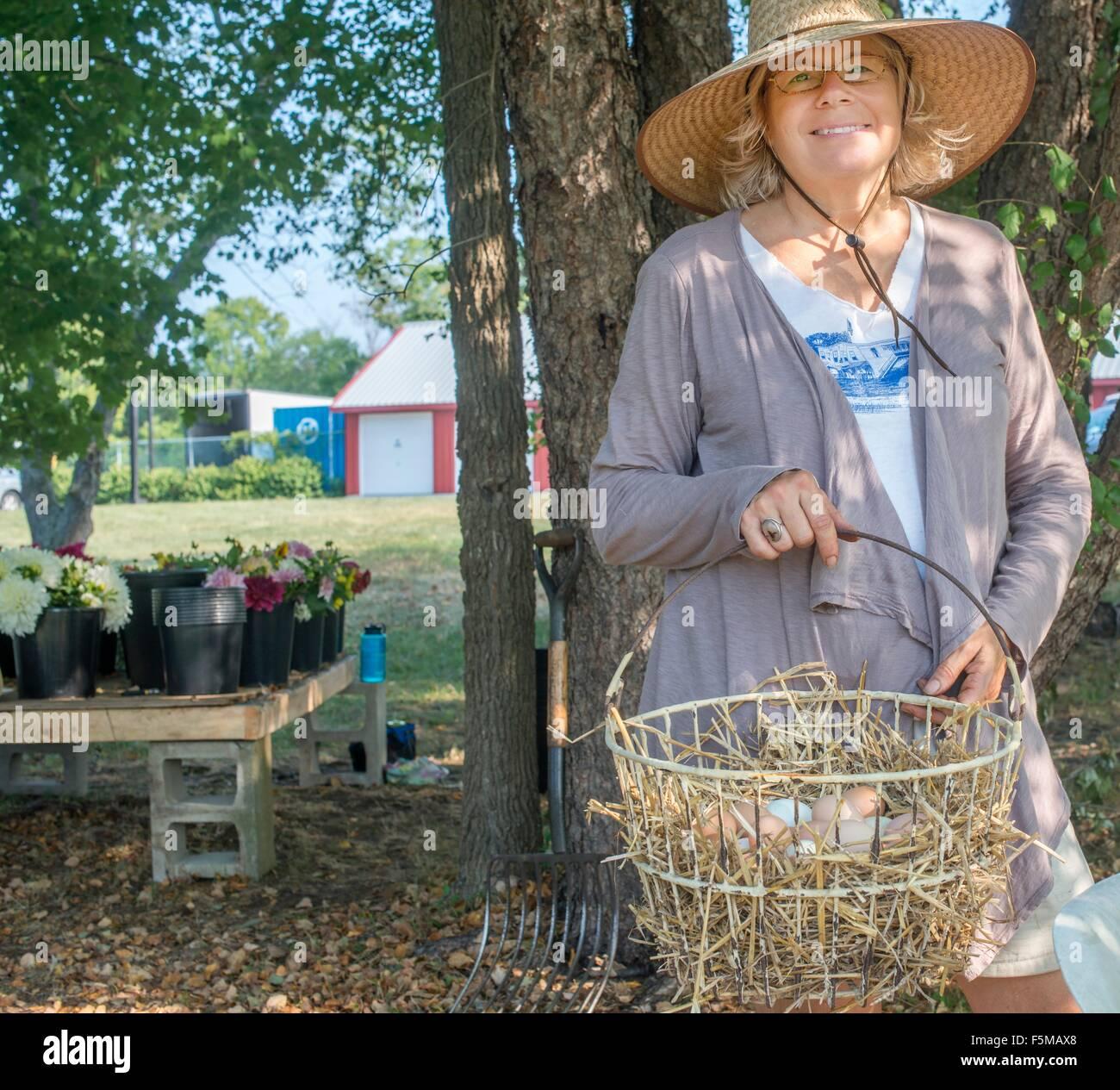 Portrait of senior female farmer carrying basket of eggs - Stock Image