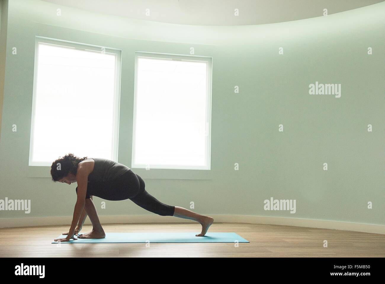 Mature woman practicing yoga in curved room - Stock Image