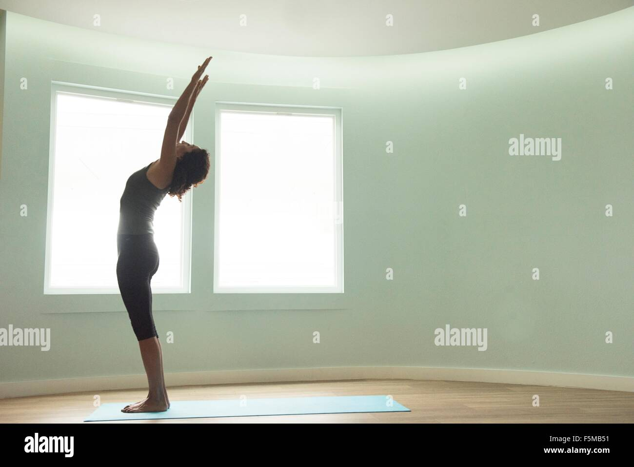 Mature woman doing yoga in curved room - Stock Image