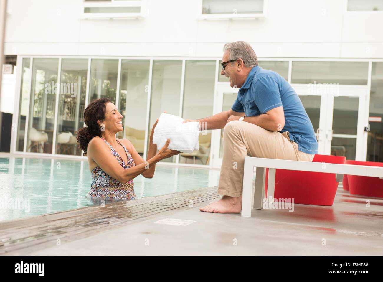 Senior man handing towel to wife from poolside - Stock Image