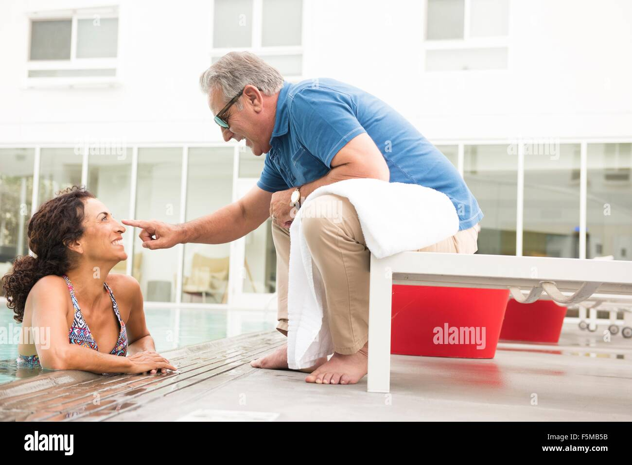 Senior man touching wifes nose from poolside - Stock Image
