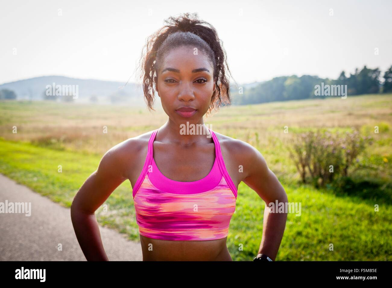 Portrait of young female runner with hands on hips in rural park - Stock Image