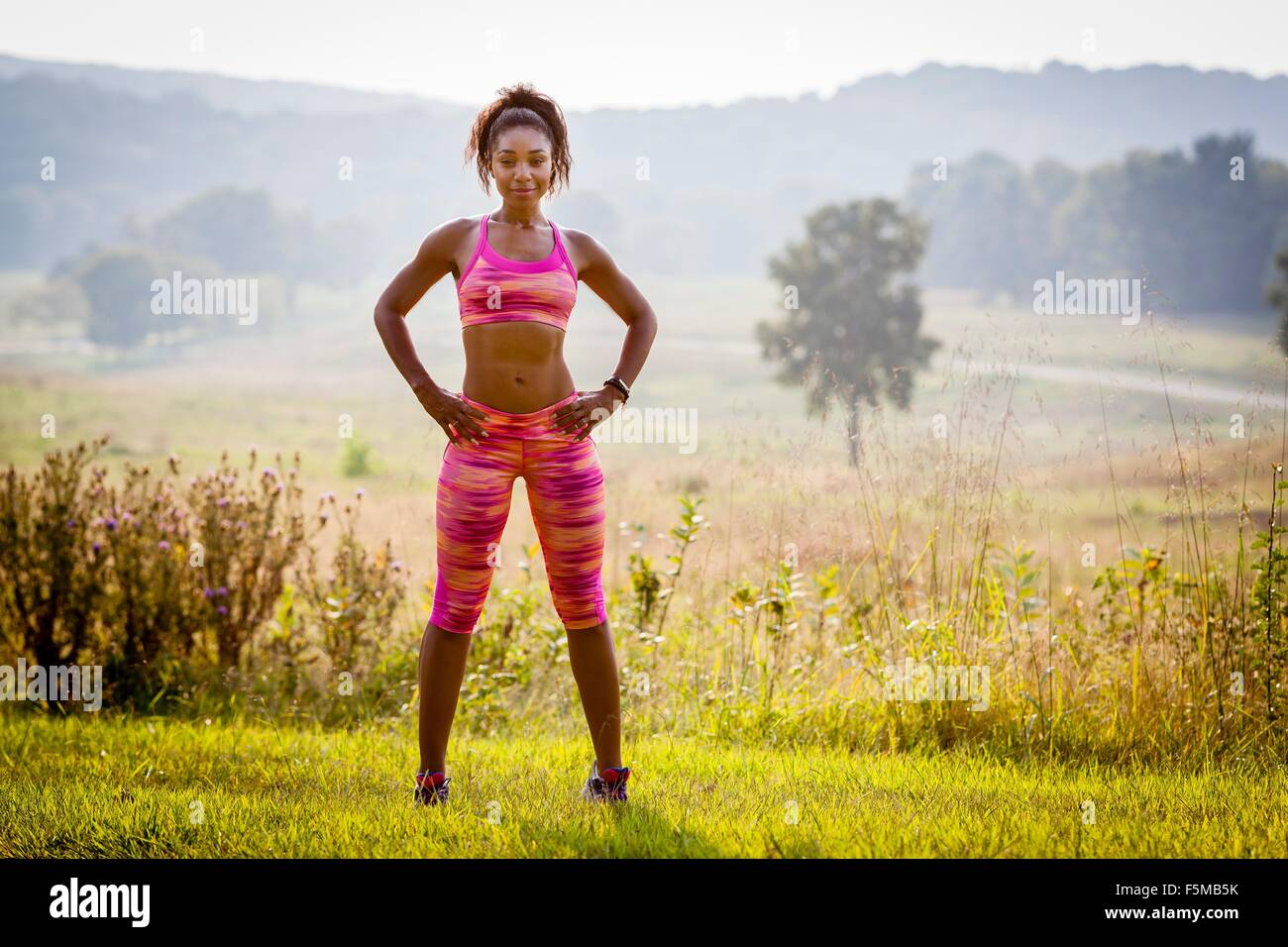 Portrait of confident young female runner in rural park - Stock Image