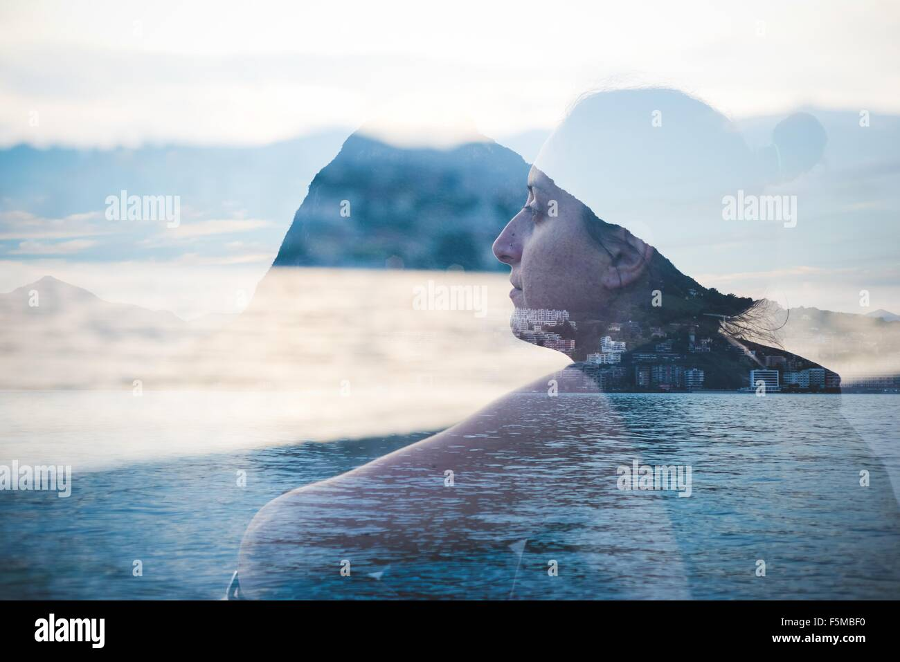Double exposure of woman looking out at Lake Lugano, Switzerland - Stock Image