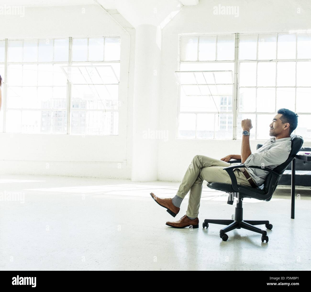 Businessman contemplating by office window - Stock Image