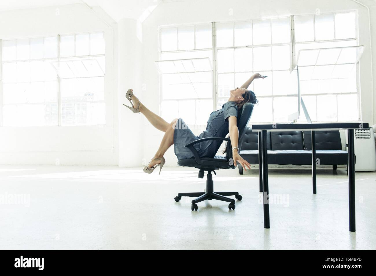 Businesswoman excited on chair by office window - Stock Image
