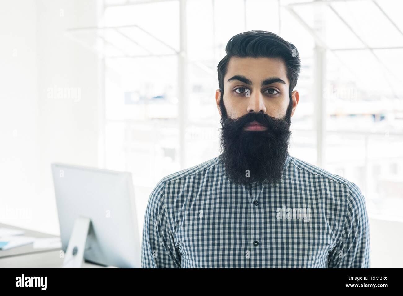 Bearded businessman by office window - Stock Image