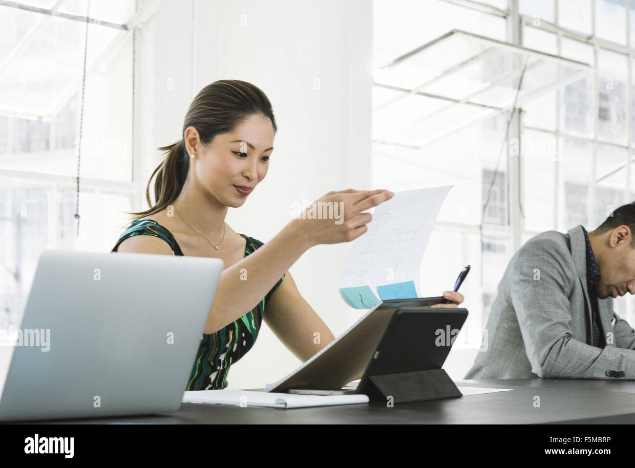 Businesswoman smiling over letter at office - Stock Image